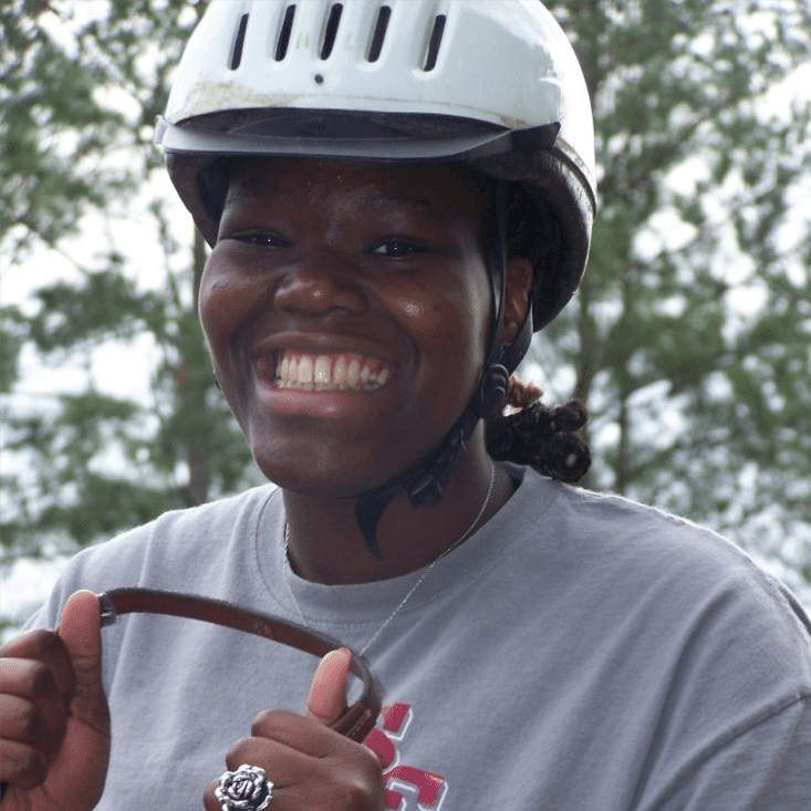 smiling girl holding reins while riding at horse at Faith ETC